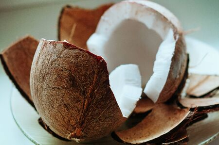 Cracked fresh coconut on white table background. Ripe half cut coconut. Coconut shell, cream and oil. Selective focus. Food ingredients, healthy lifestyle, paradise concept