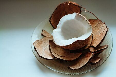 Cracked fresh coconut on white table background. Ripe half cut coconut. Coconut shell, cream and oil. Selective focus, Top view. Food ingredients, healthy lifestyle, paradise concept