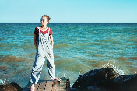 Charming girl in blue jumpers garment and sunglasses, standing on the rocky beach, sea waves behind. Summer lifestyle. Fashionable, cheerful, happy. Travel and fun concept 스톡 콘텐츠