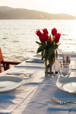 Beach restaurant with sea view at sunset, a table setting decorated with flowers. Empty porcelain plates on cloth. Beautiful summer holiday concept. Romantic dinner at resort. Selective focus