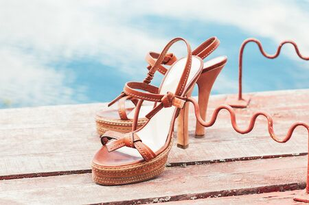 High heel brown leather vintage summer shoes, on the wooden jetty with rod rests, blue water in the background. Close up. Summer vacation, lifestyle, holiday, fashion concept. Natural light. Copy space