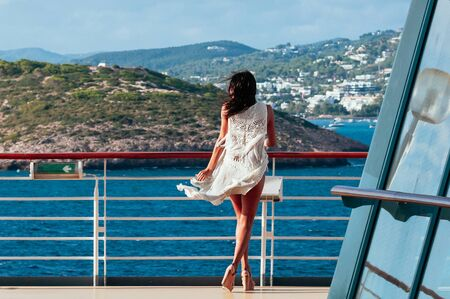 Pretty young brunette female in white dress standing on deck of cruise ship, enjoying the islands view passing by. Summer vacation, sea voyage, travel concept 스톡 콘텐츠