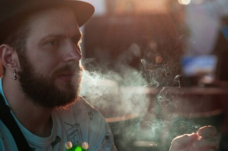 Barcelona, Spain - September 10, 2018. Handsome young bearded man in a hat, smoking a cigarette in a bar. Cropped portrait, backlight. Bad habits, environment pollution concept 에디토리얼