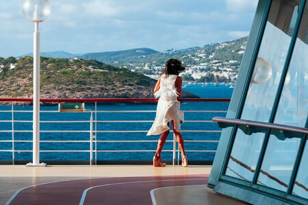Pretty young woman in white dress, standing on deck, struggling the wind, back view. Summer vacation, sea voyage, travel concept 스톡 콘텐츠