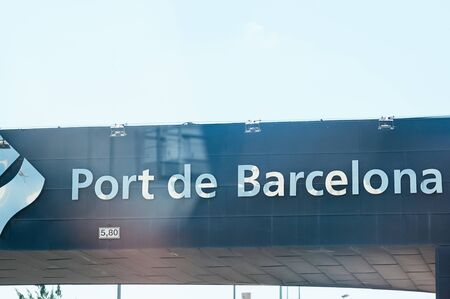 Sea Port of Barcelona, Spain - September 7, 2018. Big modern sign Port De Barcelona on the facade of the entrance gate over the road. Sunny weather. Tourist attraction. Travel to Europe concept