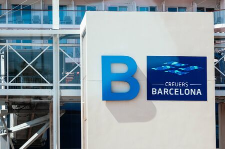 Sea Port of Barcelona, Spain - September 7, 2018. Big modern sign of cruise Terminal B, Barcelona on the facade of the entrance gate, big ship in the background. Travel to Europe concept