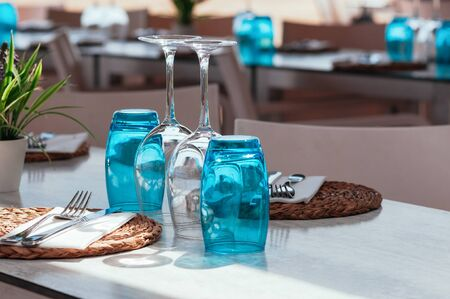 Beach cafe table setup on sunny day outdoor, served for lunch, blue glasses, wicker plates, cutlery. Authentic, simple decor. Beautiful summer holiday concept. Romantic time at resort. Selective focus 스톡 콘텐츠