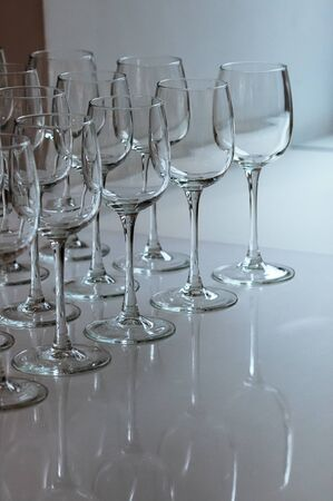 A raw of empty wine glasses on the table. Many transparent high stalk glasses on the table next to window, beautiful reflections, natural light. Catering, holiday, cafe, restaurant glassware 스톡 콘텐츠