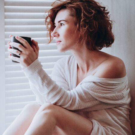 Blurred image of a beautiful young woman in white blouse, bear shoulders and legs, sitting on the window, in morning relaxation, soft light. Erotic, sensual, lifestyle concept. Square image for insta