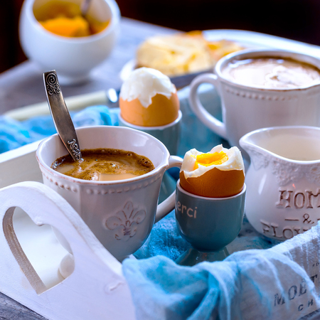 boiled eggs: Breakfast for two. Strong coffee and 2 eggs hard boiled. Eggs and coffee are located on the white wooden tray.