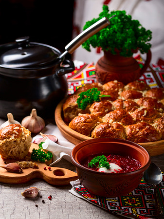 Ukrainian borsch with sour cream and herbs in a dish. Homemade dumplings with garlic. A national dish