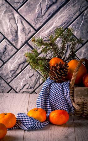 Tangerines, fir branches and pine cone in the basket. Blue cloth. Grey background Stock Photo