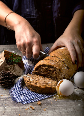 The baker slicing a knife breads. Nearby egg and flour. The concept of baking Stock Photo