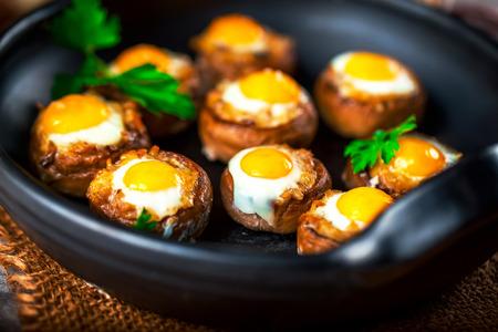 Mushrooms with quail eggs. Mushrooms on black pan. Selective focus