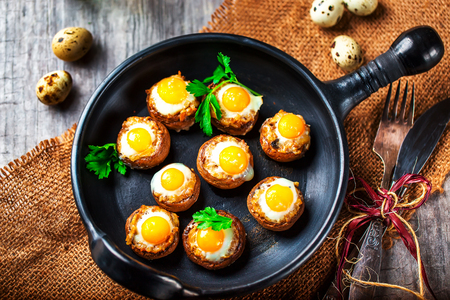 champignons: Mushrooms with quail eggs. Mushrooms on black pan. Quail eggs and cutlery close. Selective focus Stock Photo