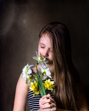 Teen girl Inhale aroma of bouquet of yellow and white daffodils. Dark background. Vertical images