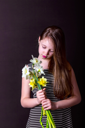 Girl holding a bouquet of daffodils. Portrait on a dark background. A vertical image. Girl in striped dress with her hair Stock Photo