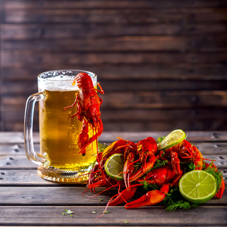 Glass of beer on a wooden background. Nearby boiled crayfishes with greens and lime. Snack to beer. Summer atmosphere. Selective focus Stock Photo