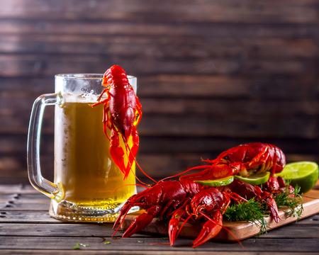 Glas bier op een houten achtergrond. Nabij gekookte rivierkreeft met groen en limoen. Snack tot bier. Zomerse sfeer. Selectieve aandacht