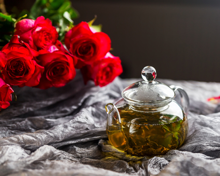 Glass teapot. A teapot with tea on the table. Glass teapot on a dark background. A bouquet of roses in the background. A bouquet of red roses next to a glass kettle