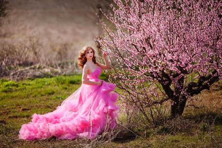 Entzückendes Mädchen in blühendem Pfirsichgarten am sonnigen Frühlingstag