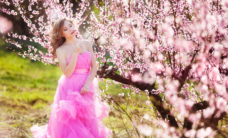 light complexion: Adorable girl in blooming peach garden on sunny spring day