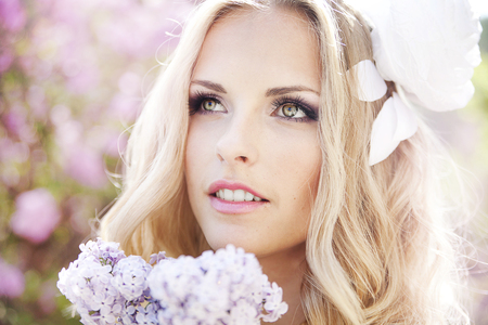 suntanned: portrait of young beautiful woman girl on background of bougainvillea purple violet flowers in blossom