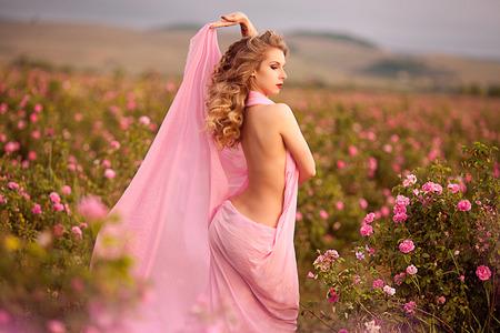 bella ragazza cammina nelle rose da giardino in un vestito rosa
