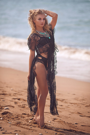 High fashion look.glamor beautiful sexy stylish blond Caucasian young woman model with bright makeup, with perfect sunbathed clean skin with jewelery in black swimsuit outdoors in vogue style