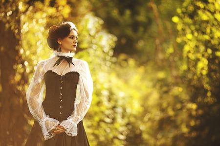 beautiful woman in vintage dress walking in autumn park.