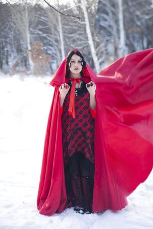 Vintage photo. girl in a long red coat walks on l ESU. Little Red Riding Hood Stok Fotoğraf