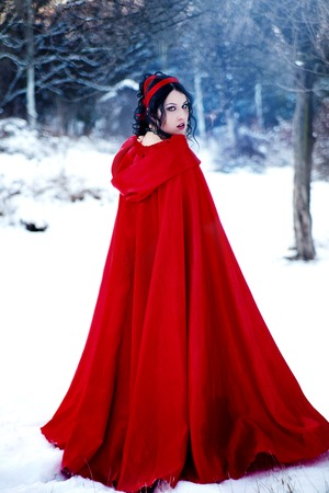 sway: Vintage photo. girl in a long red coat walks on l ESU. Little Red Riding Hood Stock Photo