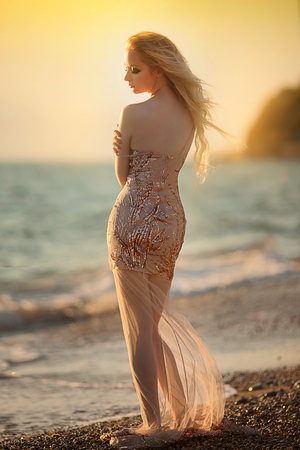 blond young woman model with bright makeup outdoors in vogue style in evening dress behind blue sky