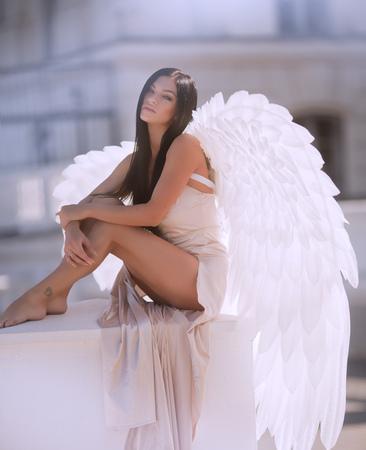Fine art photo of a woman in white dress as an angel Foto de archivo
