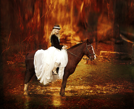 pretty woman with black horse in autumnal nature. Fashion photoshoot