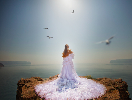 Beautiful young woman looking at the seaside. It is a sunset and she wears a white dress
