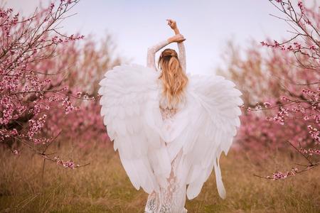 Schöne junge Frau mit riesigen weißen Engelsflügeln