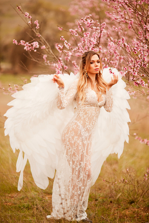 Beautiful yound woman with giant white angel wings Stock Photo - 124694307