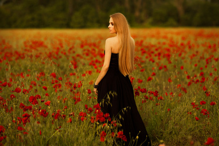 girl with a bouquet of poppies in black dress