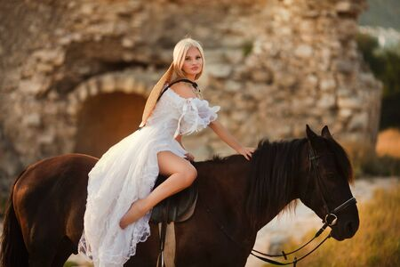 Fashionable blonde woman riding a horse in sunny day Stok Fotoğraf
