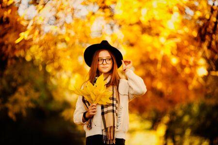 Jolie jeune femme dans un tir automnal à l'extérieur. Belle écolière à la mode posant dans le parc.
