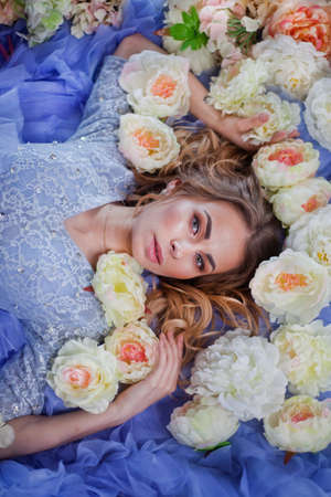 beautiful young girl in a blue dress on a bed with flowers