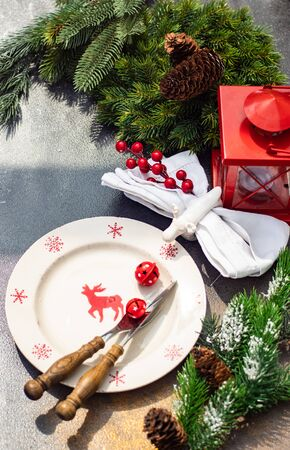 Christmas table setting concept in dark tones with red berries and fir tree