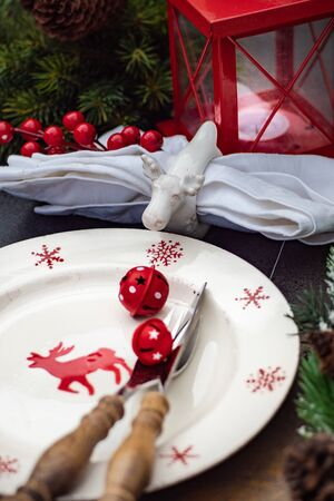 Christmas table setting concept in dark tones with red berries and fir tree Imagens - 128905317