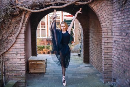 Jonge ballerina in balletkostuum dansen en pointe-schoenen is in een mooie pose dansen op straat.