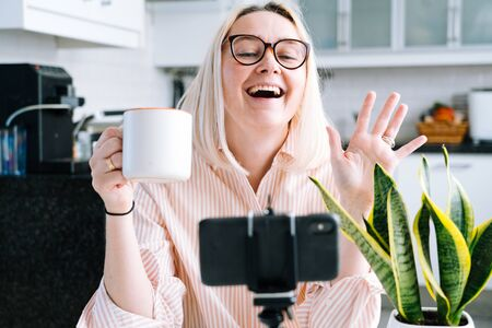 Happy girl sitting at home kitchen and holding videocall. Young woman using smartphone for video call with friend or family. Vlogger recording webinar. Woman looking camera and waving greeting hands.