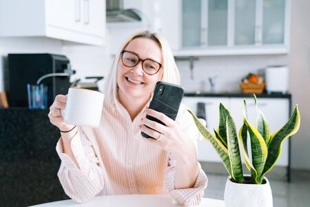 Happy girl sitting at home kitchen and holding videocall. Young woman using smartphone for video call with friend or family. Vlogger recording webinar. Woman looking camera and waving greeting hands. Banque d'images