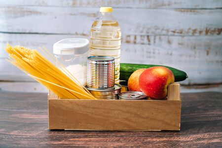 Food supplies. Crisis food box stock for coronavirus quarantine isolation period in wood background. Different food in aluminum cans, Rice, pasta, oil, fruit, vegetable. Food delivery, Donation.