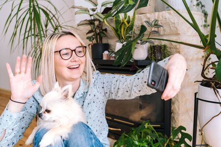 Girl sitting at living room with dog and holding videocall. Young woman using smartphone for video call with friend, family. Vlogger recording webinar. Woman looking camera and waving greeting hands.