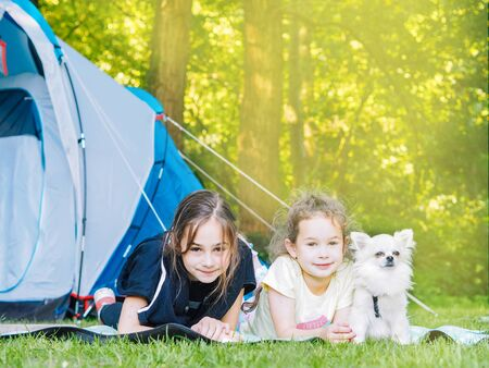 Camp in tent with children - girls sisters with little dog chihuahua sitting together near tent. Travelers sit in summer forest. Traveling with kids. Camping outdoors tourism and vacation concept.